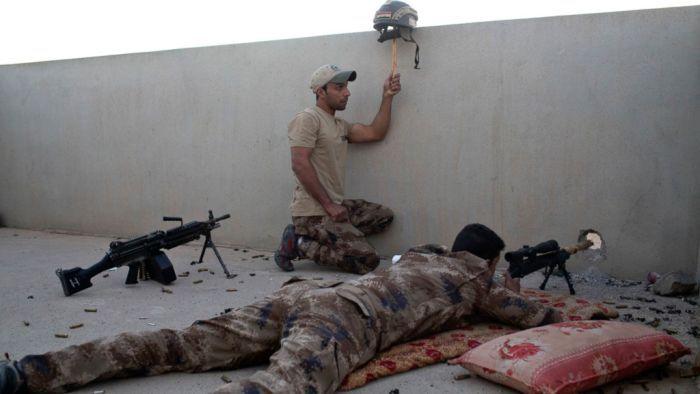 An Iraqi special forces soldier puts up a helmet as a decoy as a sniper gets ready to fire on Islamic State positions