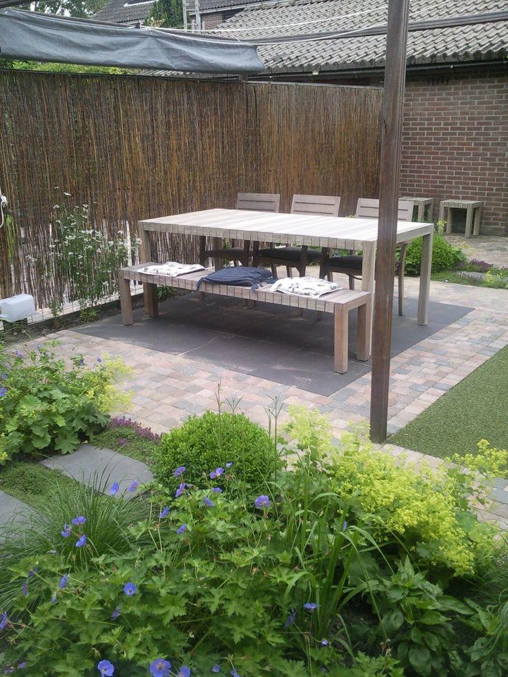 Het terras hoeft niet altijd gelijk achter het huis. We beleven de tuin immers het meest vanaf binnen! In deze tuin moet je 'door' de border de tuin in!