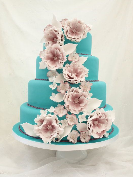the paleness of the flowers against the turquoise fondant is striking