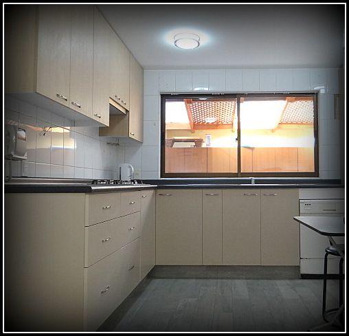 Cocina enchapada, en dos tonos, cubierta post formada, tiradores metalicos, rieles telescopicos, puertas de aluminio, brazos de gas