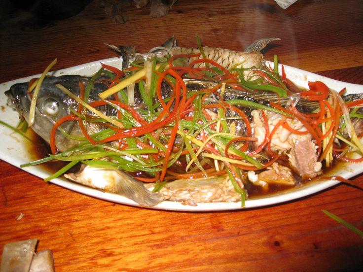 """En un restaurante, lo normal para 2 personas es pedir 2 o 3 platos (por ejemplo uno de pescado, uno de carne y uno de verdura) y arroz como base (viene a ser como el pan en Europa). En la foto, un pescado al vapor con jengibre, verduras y salsa de soja. De lo mejorcito que he comido fuera de Guangzhou (la comida cantonesa es """"otro nivel"""")."""
