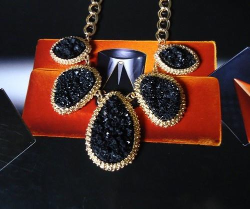 Skimrande guldfärgat halsband med hackade svarta stenar. Reglerbart spänne bak.