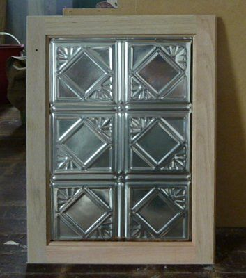 Tin ceiling tiles used as cabinet door panels.