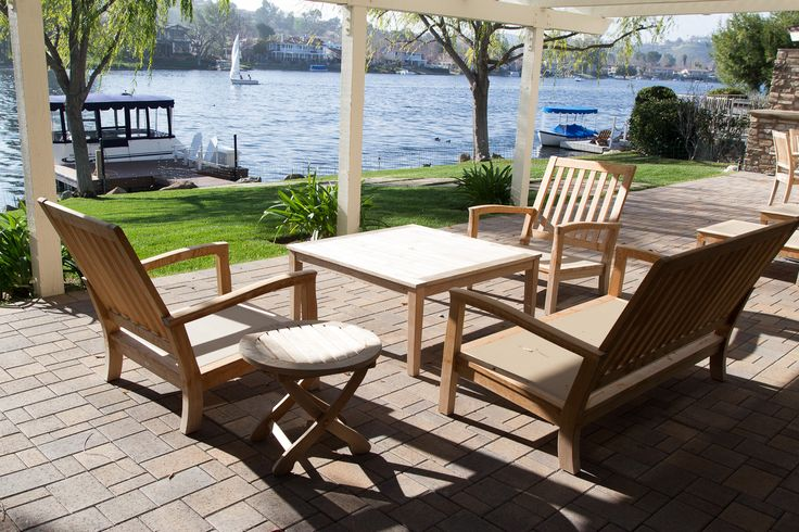 White wooden pergola covers a brick paved floor. The patio offers a great view of the lake. What kind of things do you like to do at the lake? #patio #patioideas #patiodecor #patiodesign