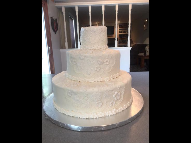 Wedding Cake.  Buttercream frosting smoothed.  Floral fondant embellishments with fondant flower boarder.  Fondant molds can be found at Joann Fabrics or your local cake supply store as well as on Amazon.