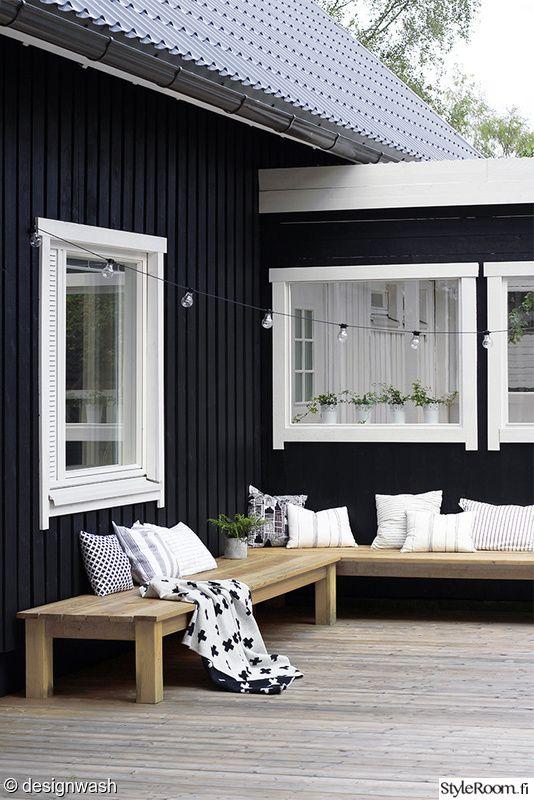 L字型に配置された木製の低いデイベッドのあるウッドデッキの屋外リビング