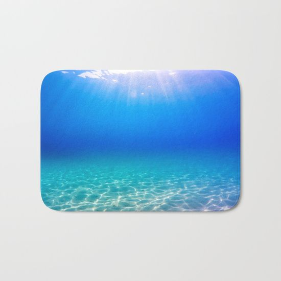 Underwater picture taken in Greece on a beautiful sandbeach with crystal clear water and the sun rays shining through the surface, creating a display of glowing patterns on the bottom. #underwater #water #sea #ocean #beach #summer #travel #adventure #blue #swimming #freediving #diving #homedecor #bathmat #mat