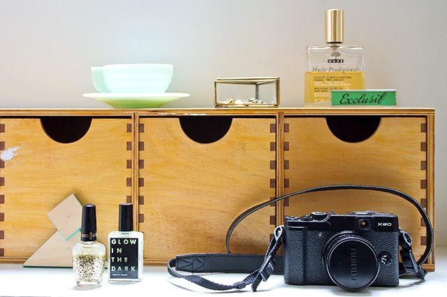 Casiers + tasse + boite en verre dégotés dans un vide grenier, Huile Prodigieuse Nuxe, Vernis à paillettes gold Milani, Vernis « Glow in the dark » American Apparel, Appareil photo X20 Fujifilm
