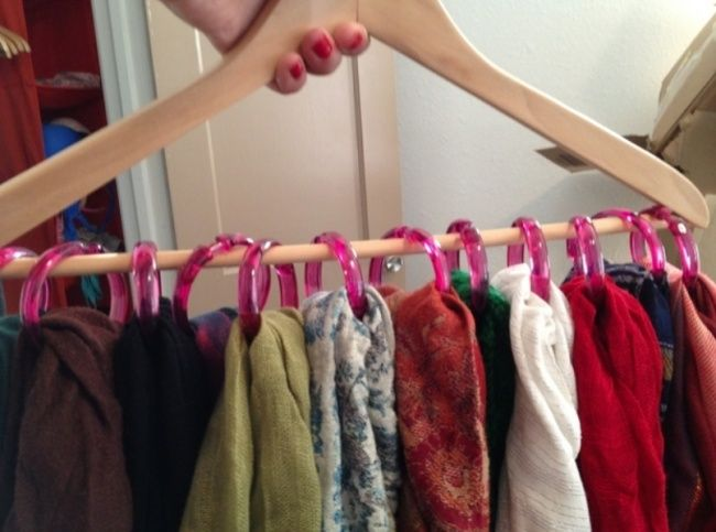 With the help of a coat hanger and the rings from a shower curtain, you can solve the problem of where to hang your scarves