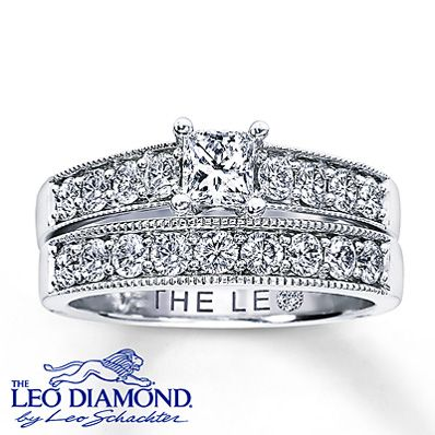 This romantic Leo Diamond bridal set features an engagement ring with a beautiful princess-cut diamond surrounded by dazzling round Leo diamonds. The wedding band displays round Leo Diamonds set in 14K white gold. With a total diamond weight of 1 1/4 carats, these fine jewelry rings feature independently certified Leo diamonds, and the unique laser-inscribed Gemscribe® serial number ensures your peace of mind. Available online while supplies last.