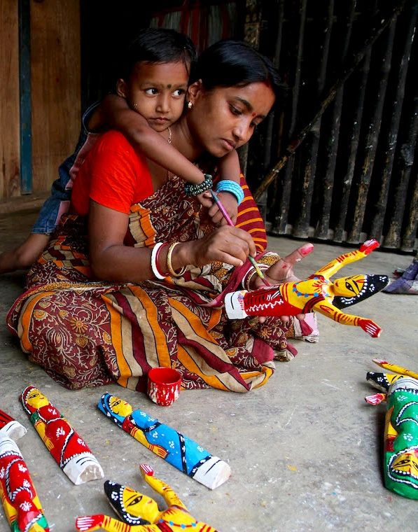 A craftswoman paints hand made wood figurines while straddling her daughter on her back.
