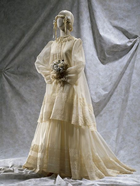Instantly recognisable as a Gina Fratini, this layered, floating wedding dress has a smock-like top and long, full sleeves. l Victoria and Albert Museum