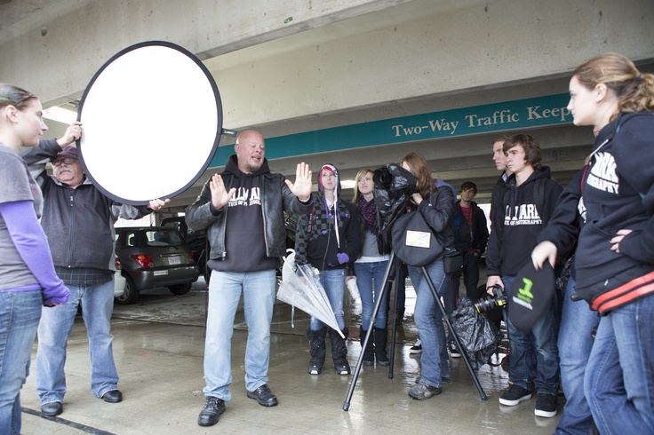 A little (or more like a lot) of rain was not enough to stop students and faculty from carrying out their back light assignment on a field trip to Northampton, MA. Here, Instructor Rich Barnes explains how to create dimensional light in the otherwise non-dimensional situation of the parking garage. Instructor Dick D'Alessandro demonstrates, as Rich addresses the students.    Photo: David Turner