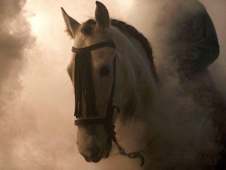 Een man rijdt op zijn paard door de rook van de vreugdevuren om hem te 'zuiveren'.