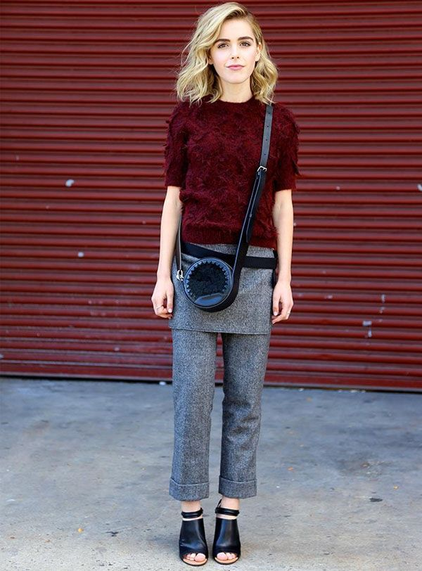 Kiernan Shipka wears a 3.1 Phillip Lim burgundy sweater, wool pants, and black ankle-strap heels