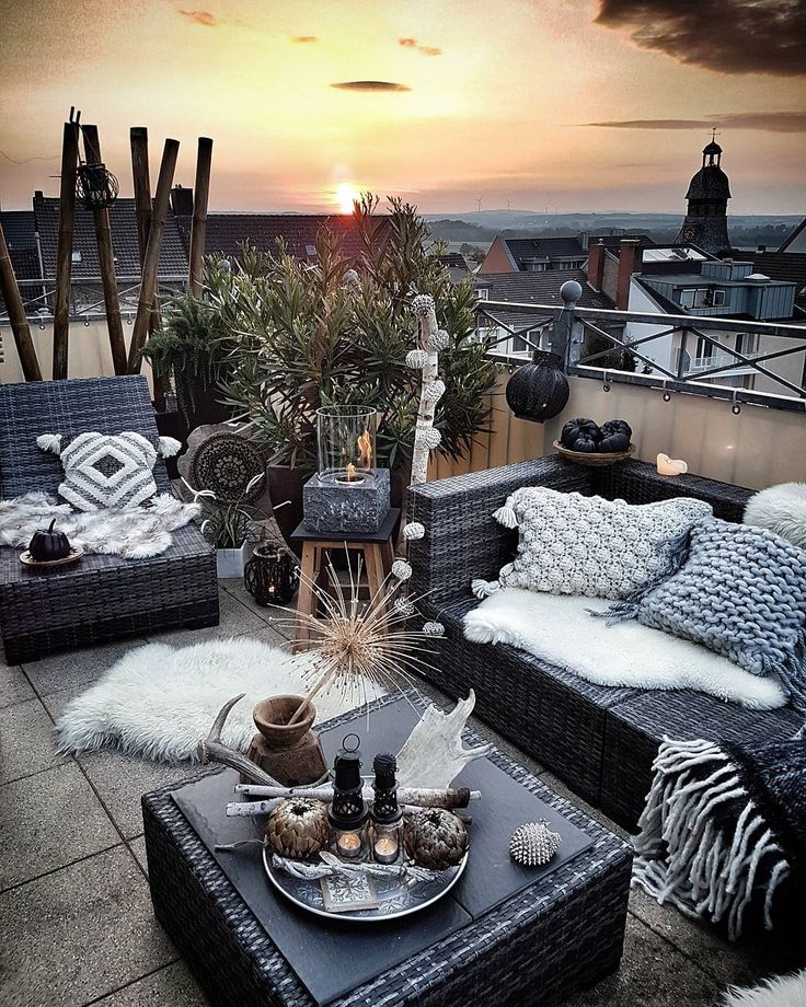 balcony with black wicker lounge seating, coffee table, and shades of gray and white accent pillows