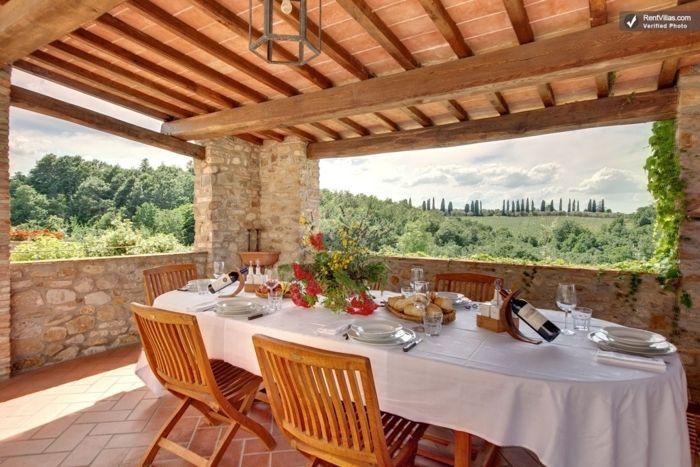casas rurales baratas, terraza de piedra y techo de madera, comedor con vista, mesa y sillas de madera