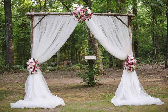 rustic branch ceremony arch with draped tulle and floral accents