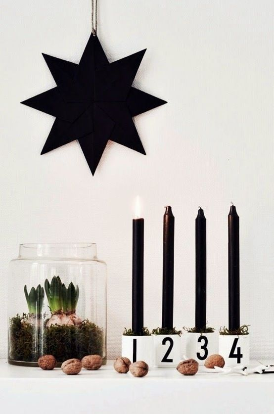 Minimalistic advent decoration with black candles and green moss.