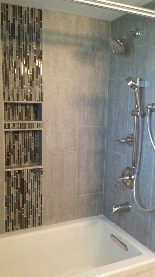 "Small alcove shower tub with Malta Gray porcelain tile surround and ""Dusk to Dawn"" linear glass mosaic tile running vertically through stacked niche."