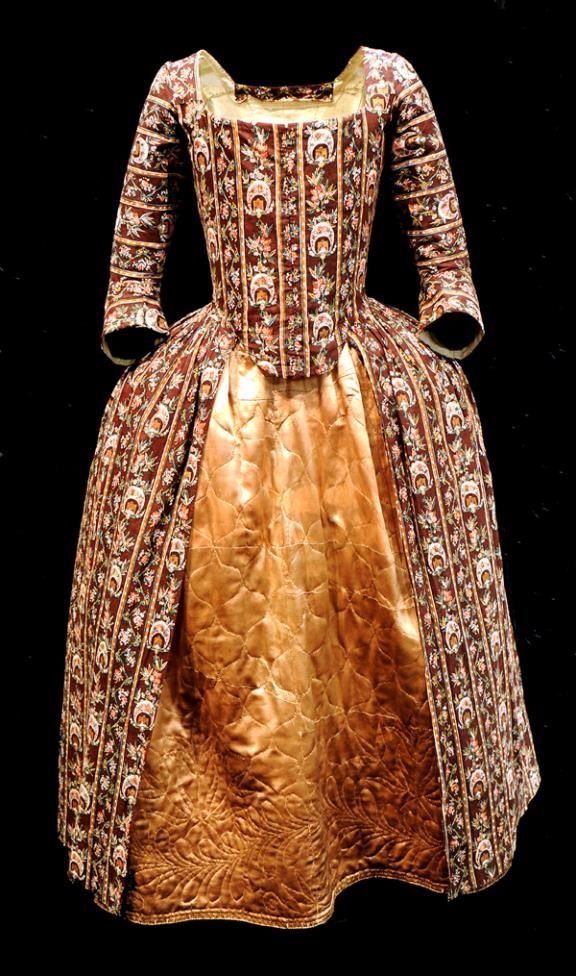 Robe à l'anglaise, England, 1770-1780. Hand block printed cotton, called 'dark ground chintz'; quilted gold silk satin petticoat.