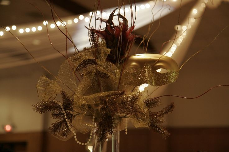 Fantastic Masquerade Party Centerpiece: feathers, mask, branches, etc http://www.mybigdaycompany.com/masquerade-ball.html