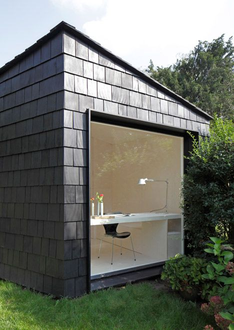 This garden studio features a plywood-lined interior and is covered in cedar shingles.