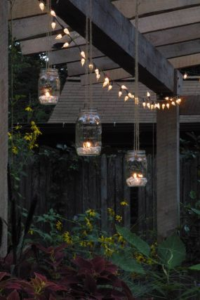 Create inexpensive, home-made garden lanterns with some twine, a few Mason or Ball jars, some sand or glass beads, and a few tealights.