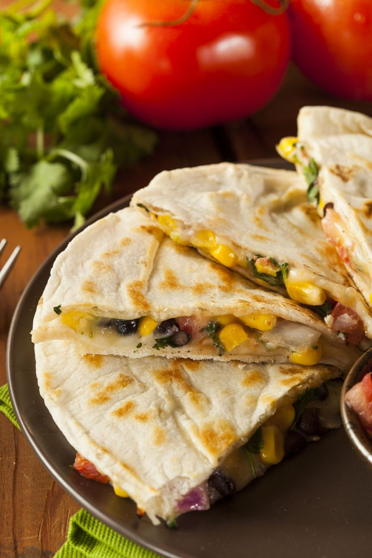 vegetarian quesadillas filled with spicy corn and black bean mixture and cheese on a natural wood serving platter (with bark exterior) Find this Pin and more on LUNCH / SANDWICHES / WRAPS by It's Yummi | Recipes, Home Living and Wellness. Bites of food and life. Vegetarian quesadillas will be a welcome entree for a meatless Mexican dinner or lunch.