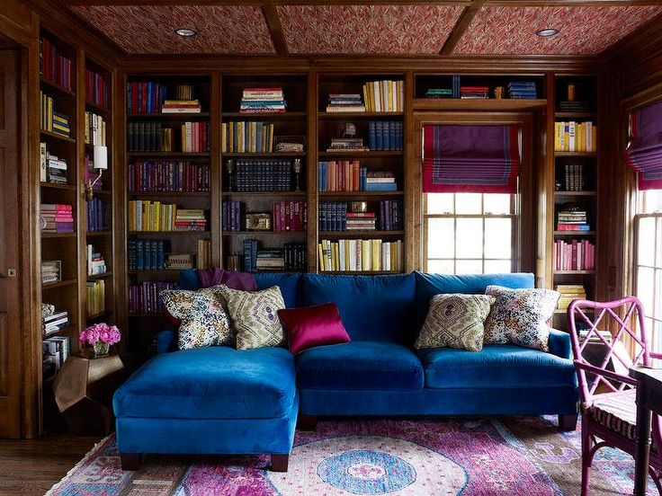 Jewel box den features a ceiling wallpapered in Pheasant by Twigs Wallpaper atop a pink and gray rug by Stark lining a wall fitted with floor to ceiling bookshelves, with books organized by color, alongside a lavender bamboo chair painted benjamin Moore Mulberry.