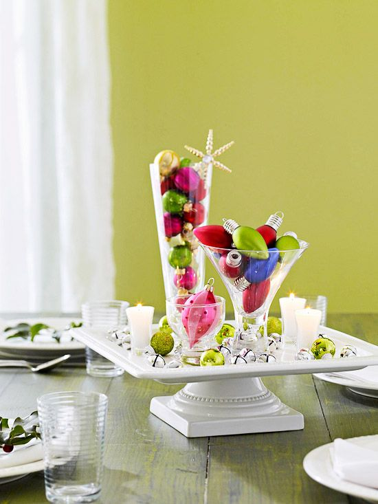 fill a few glasses with ornaments and arrange on a footed cake plate. cover the base with extra ornaments, bells, candles