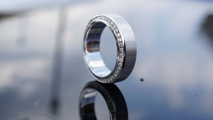 """Mens """"JustPerfect"""" wedding band in white gold with bezel set round diamonds on outer sides."""