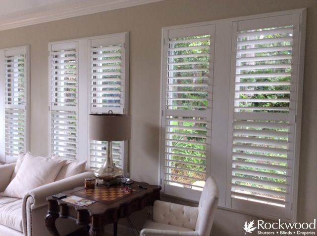 White shutters with wide t-posts, divider rail, hidden ...