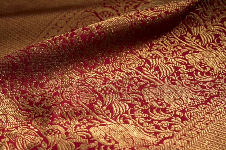 The richly woven zari on this stunning red sari has intricate motifs of animal life.