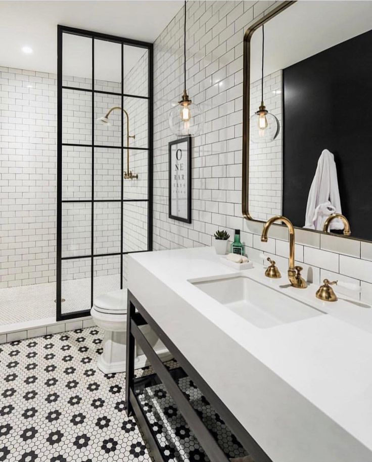Black and white bathroom with classic and modern finishes. brass fixtures   glass pendants   half shower wall   hexagon tiles