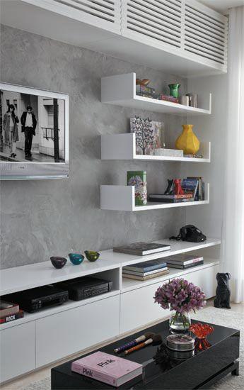 Parede de cimento queimado e prateleiras brancas é uma grande ideia para a sua sala.