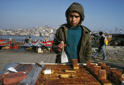 Most nations have laws that prohibit child labor. Yet throughout the world, children in large numbers can be seen toiling in sweatshops, hauling concrete, tilling fields, plucking garbage or peddling shoes.     A Turkish boy selling bricklike sweetcakes on an Instabul street.  01 January 1978  Istanbul, Turkey