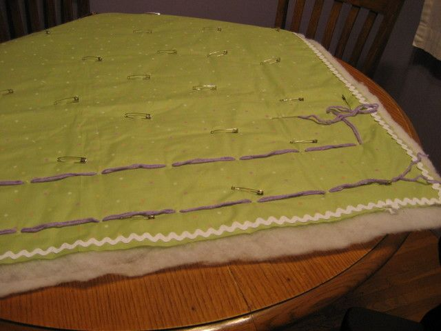 Hand tying a quilt.