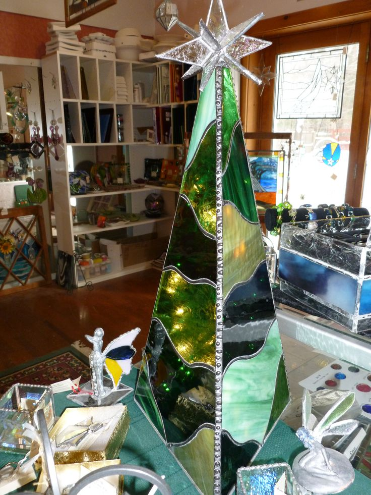 Three sided 3D stained glass Christmas tree with a variety of shades of green.  Lighted from within with a string of sparkling Christmas lights.  This table top tree will adorn any home with the warmth of the Christmas holiday. #StainedGlassChristmas