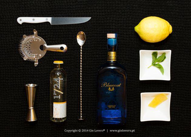 """GBluecoat T 1724 B Limão, hortelã O Gin Bluecoat ostenta orgulhosamente o moto """"American Dry Gin"""". É um dos Gins que está empenhado em definir este novo estilo de Gin – distanciando-se do London Dry Gin – diminuindo a quantidade de zimbro e aumentando os citrinos. O resultado"""