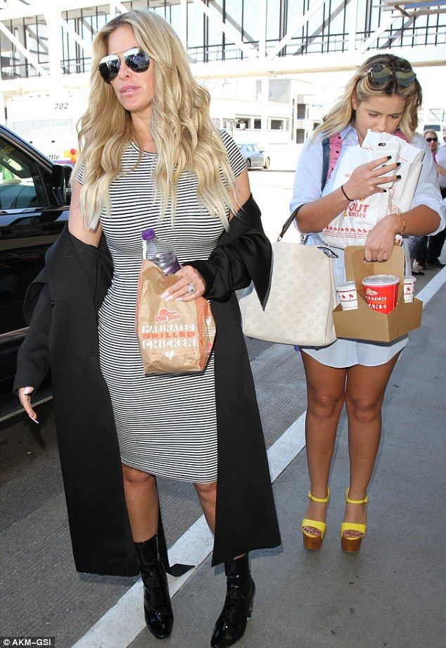 Food on the go: Kim Zolciak and her daughter Brielle arrived at LAX on Thursday with armfu...