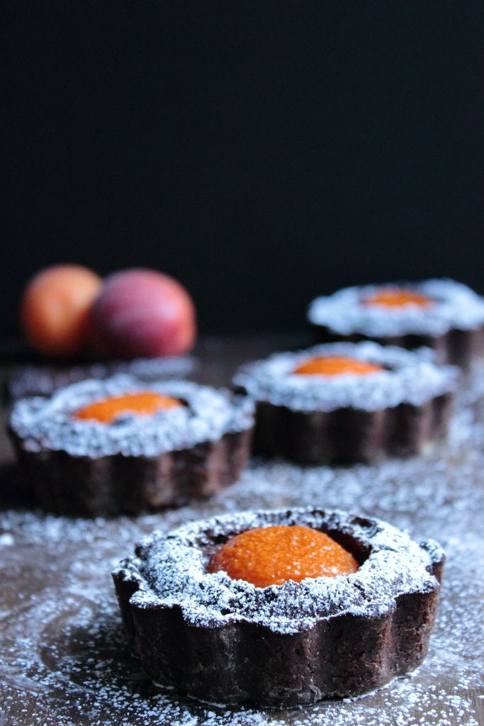 Amazing looking dark chocolate tarts with plump, fresh apricots nestling in the middle. Damn they look good!