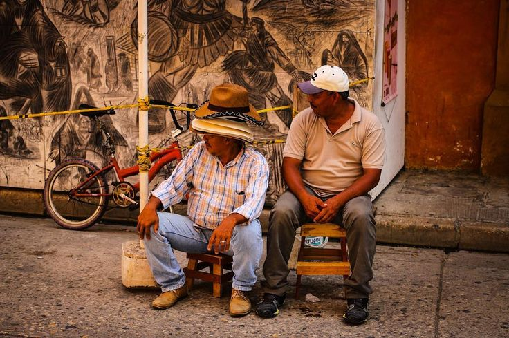 A street photography shot from Cartagena in #Colombia. These two men were looking at my friend who was taking a picture of a mural nearby. I thought this situation looked quite funny when their positions were in unison so I took their picture. Men like these selling hats were present in every town around Colombia but especially in Cartagena.