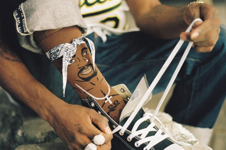 "The memory of Tupac Shakur, famed rap icon and pop culture phenomenon, lives on through Stance's new ""Legend""  sock collection.  The late superstar was one of the music industry's best-selling artists until he tragically lost his life during an infamous Las Vegas shooting in 1996.  Tupac's image has been immortalized by two different sock designs; one featuring a photograph of Shakur showing off his signature ""Thug Life"" abdomen tattoo and another that includes a front-facing bandana…"