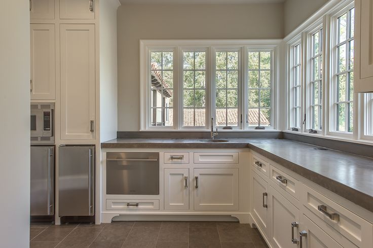 Chic butler's pantry features creamy white shaker cabinets fitted with a pull-out dishwasher ...