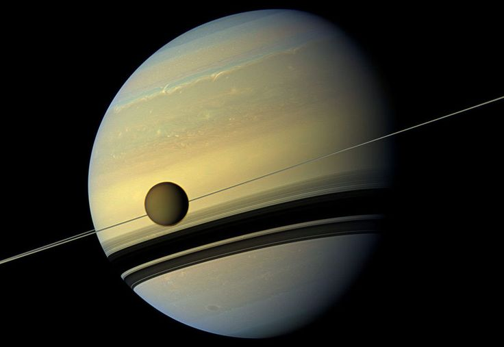 A giant of a moon appears before a giant of a planet undergoing seasonal changes in this natural color view of Titan and Saturn from NASA's Cassini spacecraft, on May 6, 2012.
