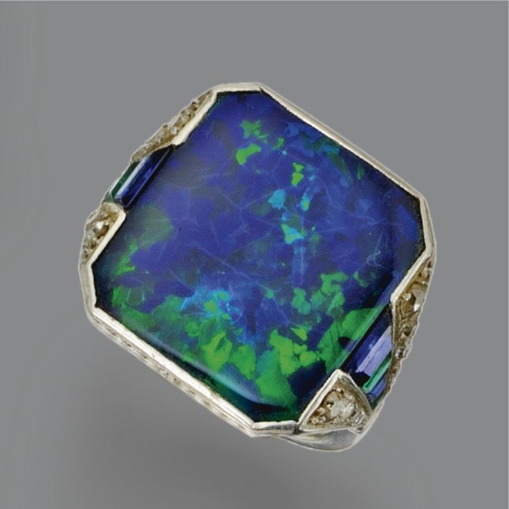 BLACK OPAL, COLORED STONE AND DIAMOND RING, CIRCA 1930 The black opal of rectangular shape with cut-corner edges measuring approximately 16.5 by 15.0 mm., the shoulders set with tapering bands of calibré-cut emeralds alternating with calibré-cut sapphires within borders of small single-cut diamonds, mounted in platinum