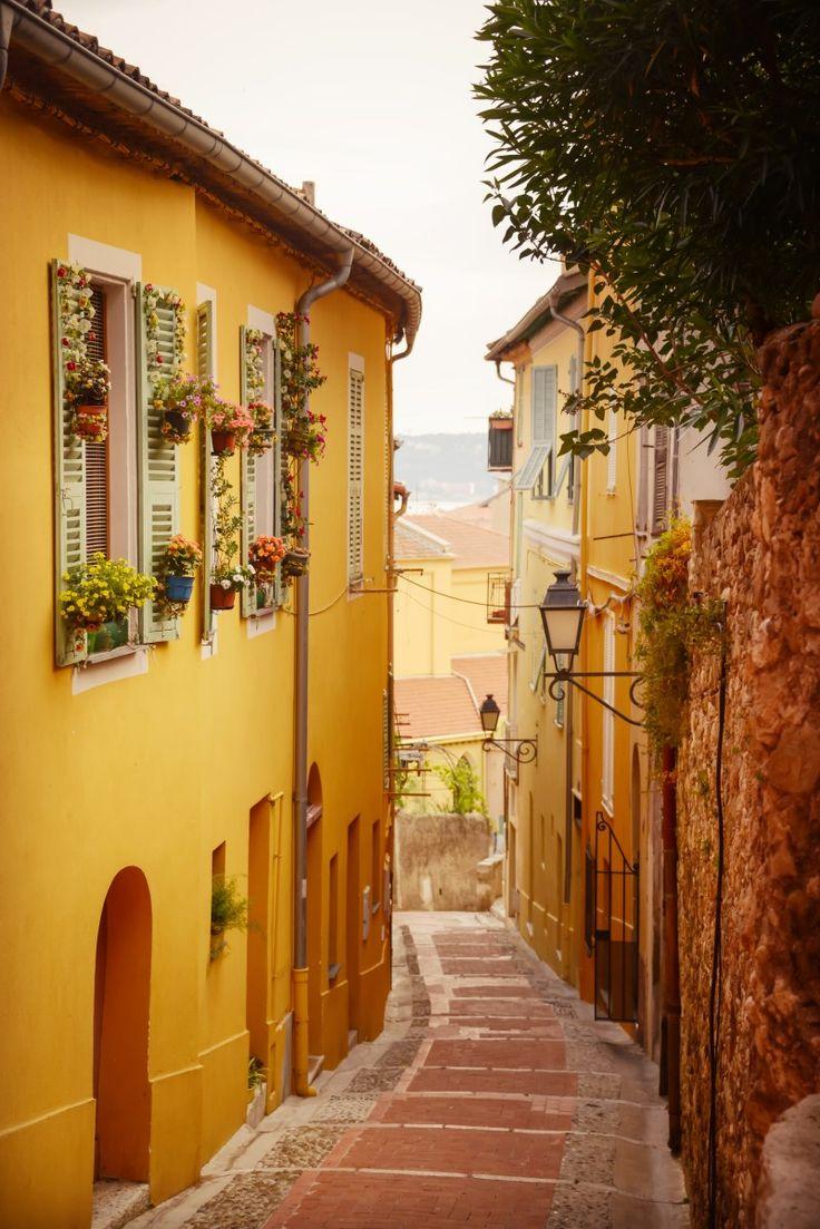 Menton, France - quaint alleys, vibrant art scene and bright facades overlooking sandy shores.