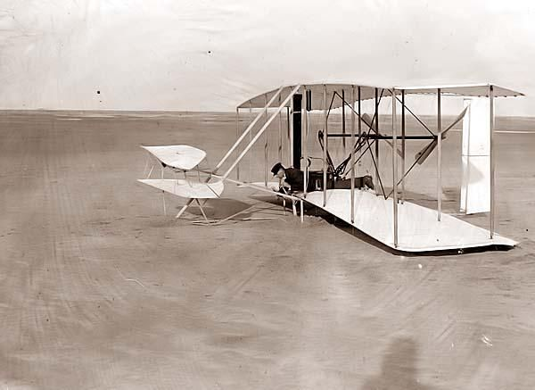 Wilbur Wright in prone position in damaged flying machine on ground after unsuccessful trial of December 14, 1903; Kitty Hawk, North Carolina.
