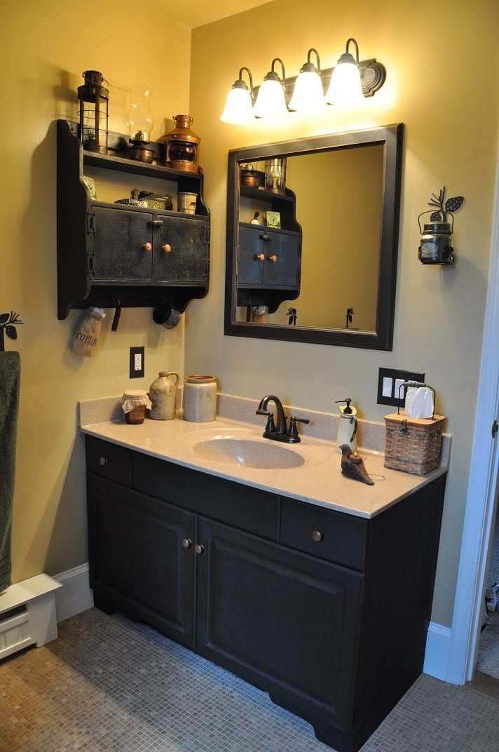 country bathroom with black vanity mirror and wall cabinet also black faucets